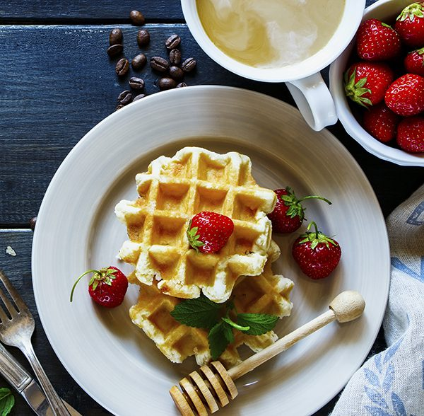 Breakfast homemade waffles stacked on a plate, served with coffee, fresh strawberries and mint at textile napkin over old wooden table. Flat lay. Dark rustic style